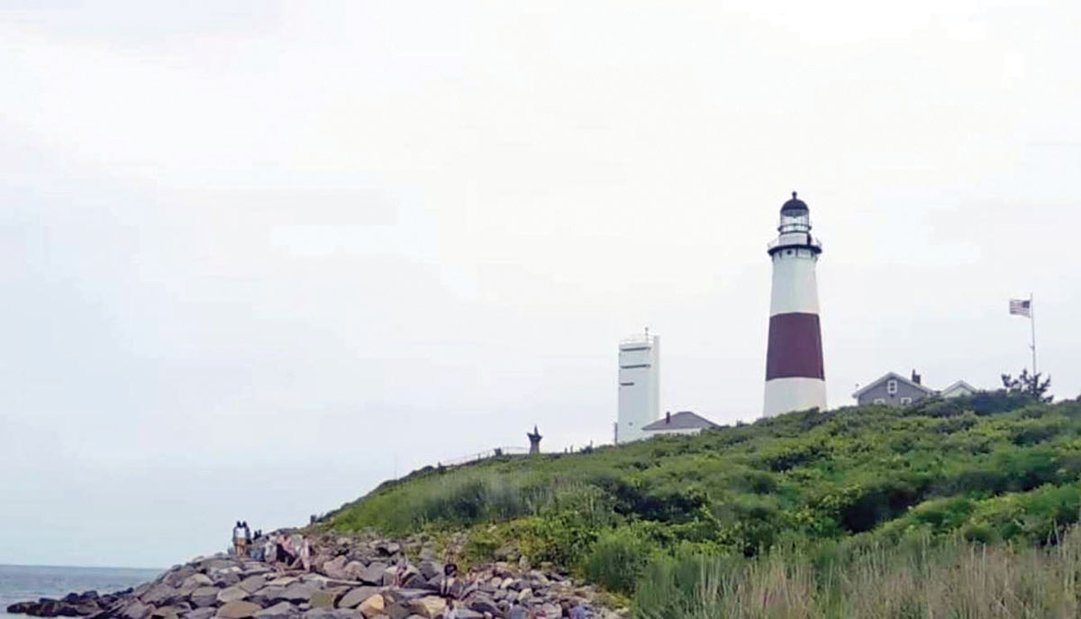 View of a lighthouse on the edge of an island near the rocks