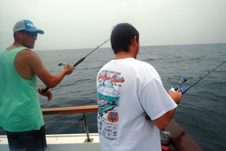Two men in a boat on holding fishing rods