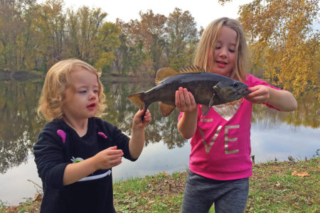 Two girls showing off a black fish