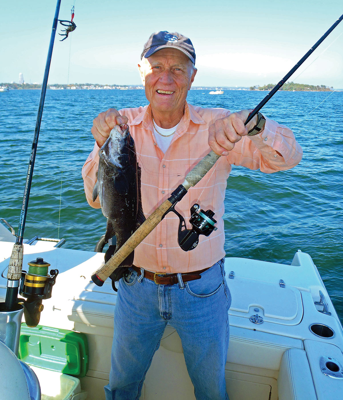 Man holding a fishing rod and a black fish in a boat