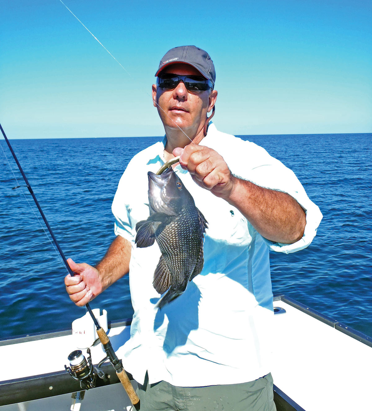 man in white shirt holding a fishing rod and black fish in a boat