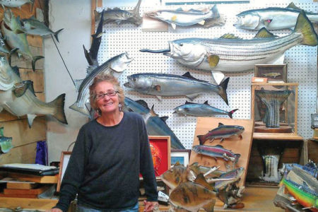 Janet Messineo smiling inside her taxidermy studio
