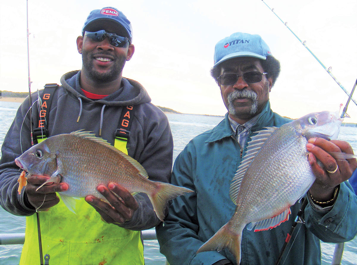 Two men in caps and sunglasses showing off their fishes