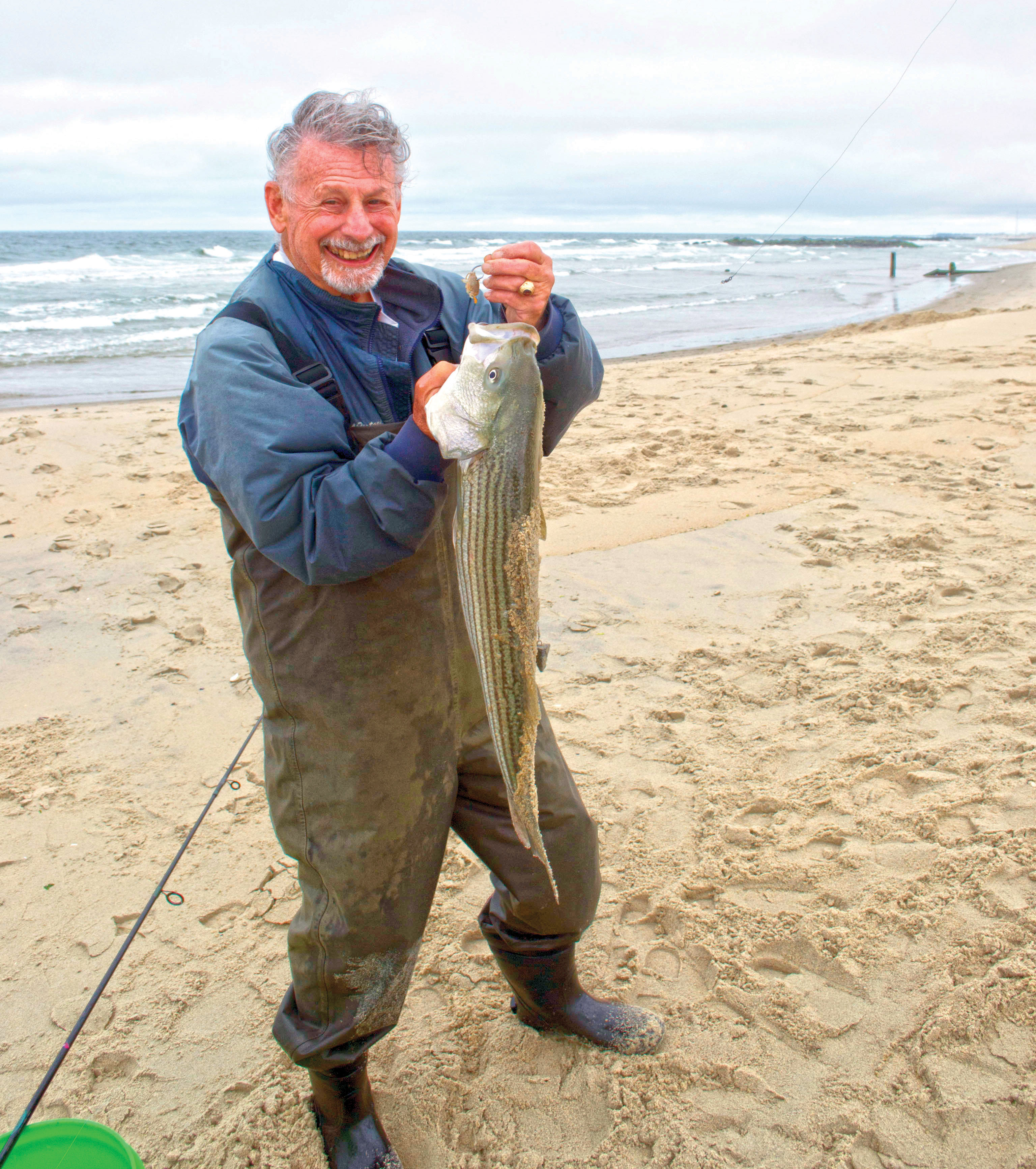 Man in jumpsuit in the sand holding the fish he caught