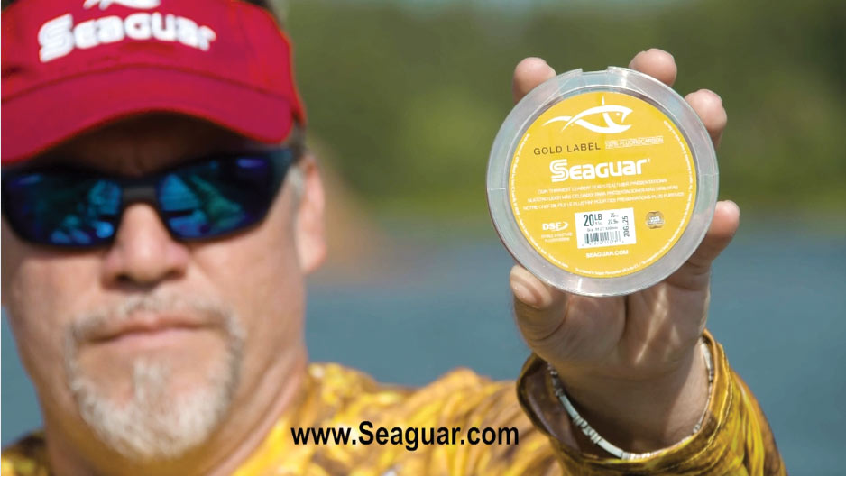 man holding seaguar gold label to camera