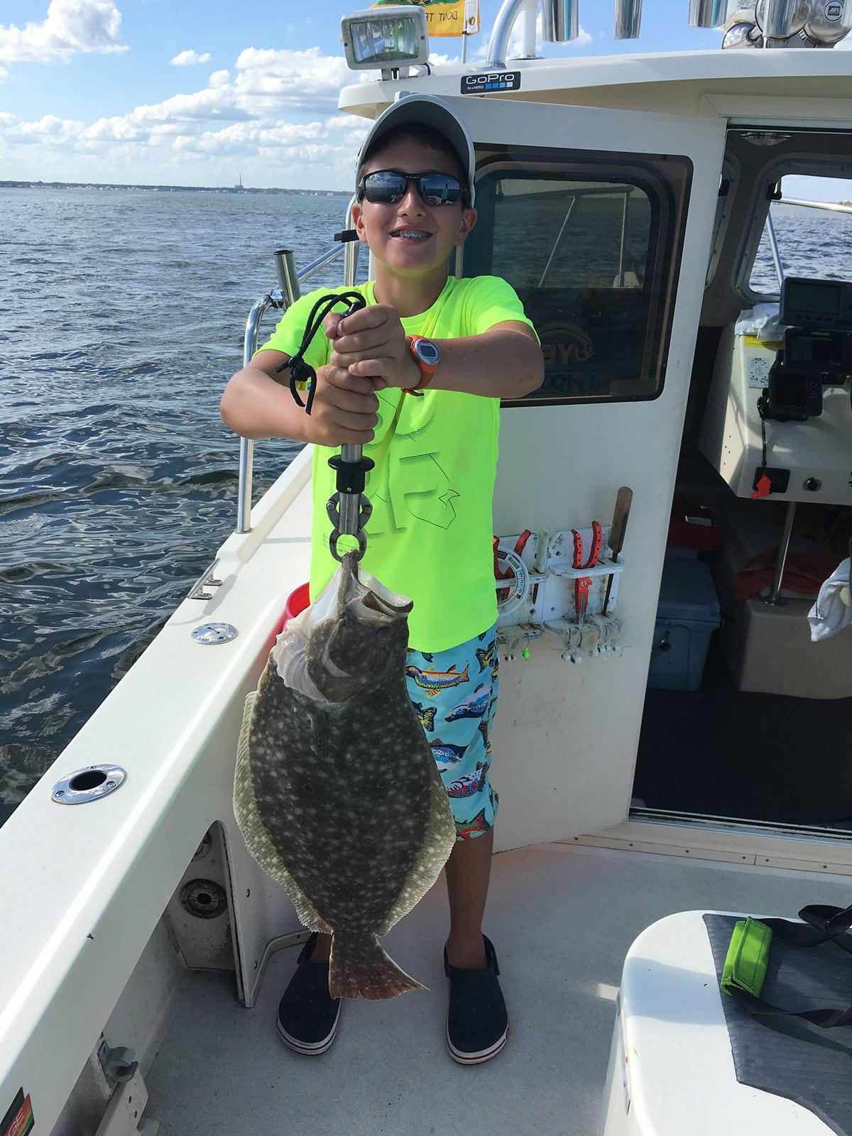 boy in neon shirt showing off the fluke fish he caught