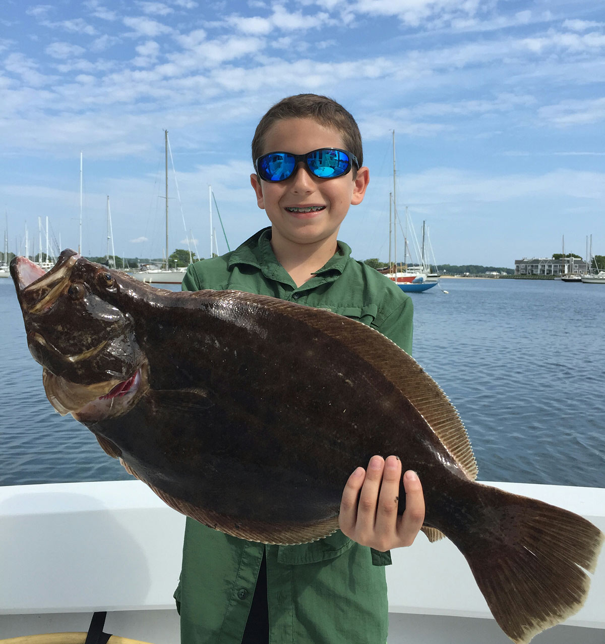 boy in a boat holding up the flume fish he caught