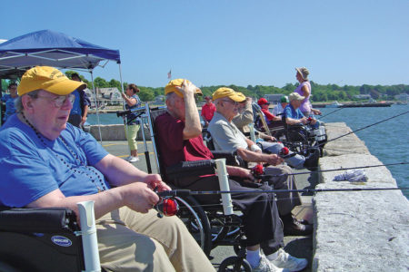 Group of senior citizens in wheelchair from the Sacred Heart Nursing Home enjoying fishing off a pier