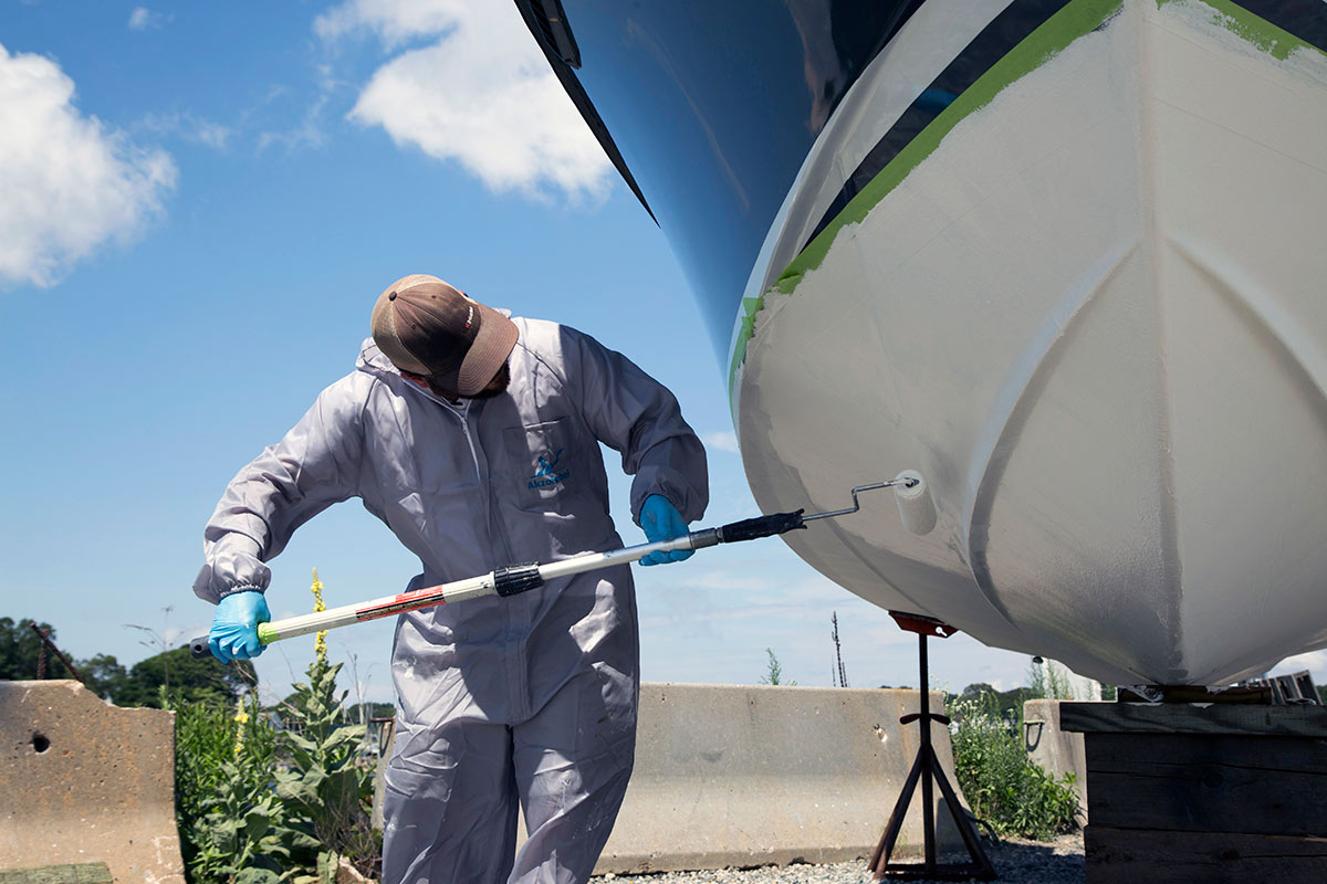 man in jumpsuit painting the bottom of a boat with white paint
