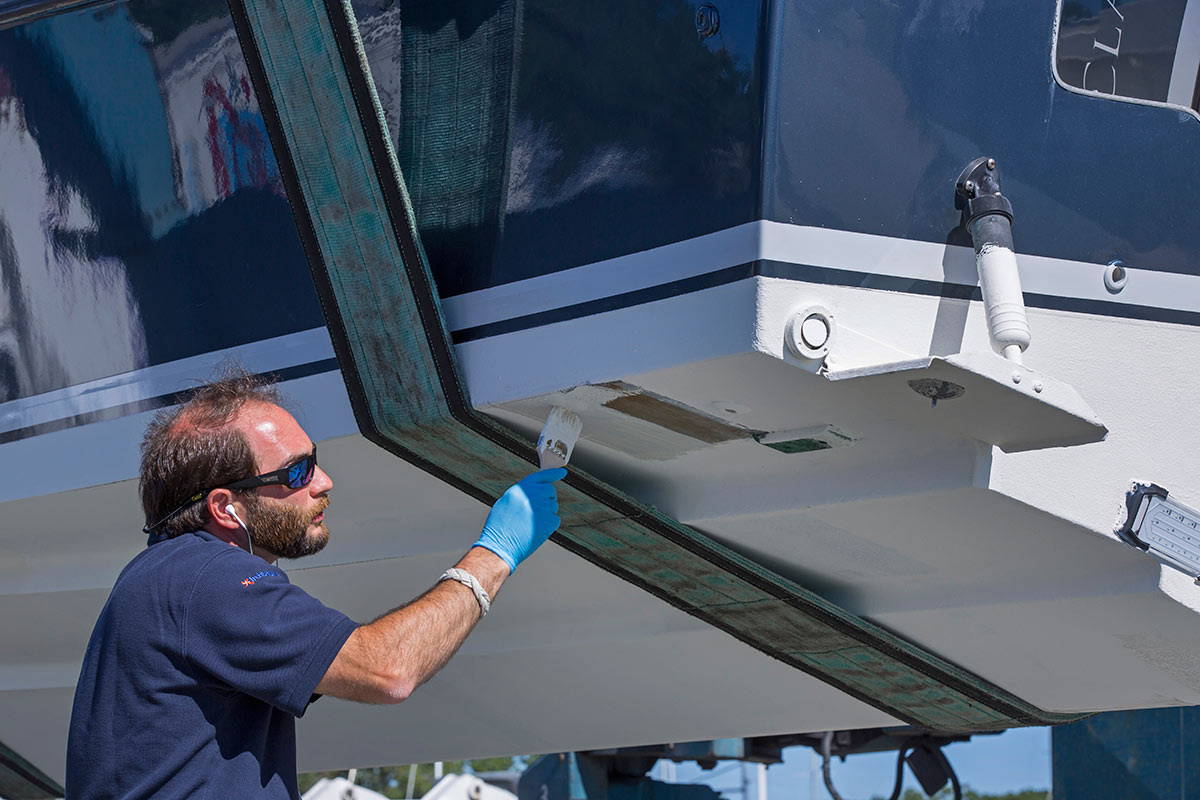 man painting the bottom of a boat with white paint