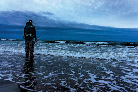 Man standing in the shore holding fishing rod