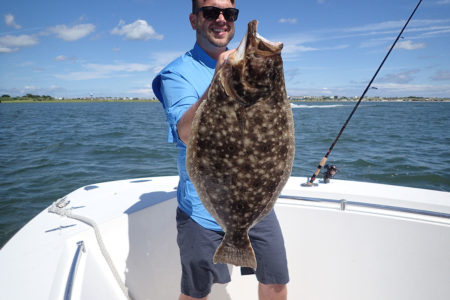 A man in blue shirt shows off the big fluke he caught
