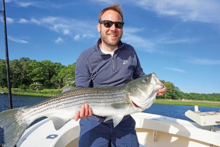 Man in glasses showing off a huge striped bass