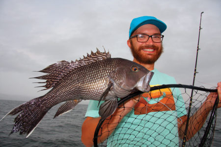 Man in cap with black sea bass. fish net and rod