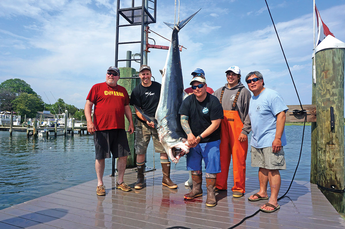 Six men crew smiling with mako shark they caught