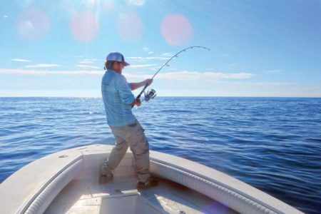 Man on a boat holding a fishing rod