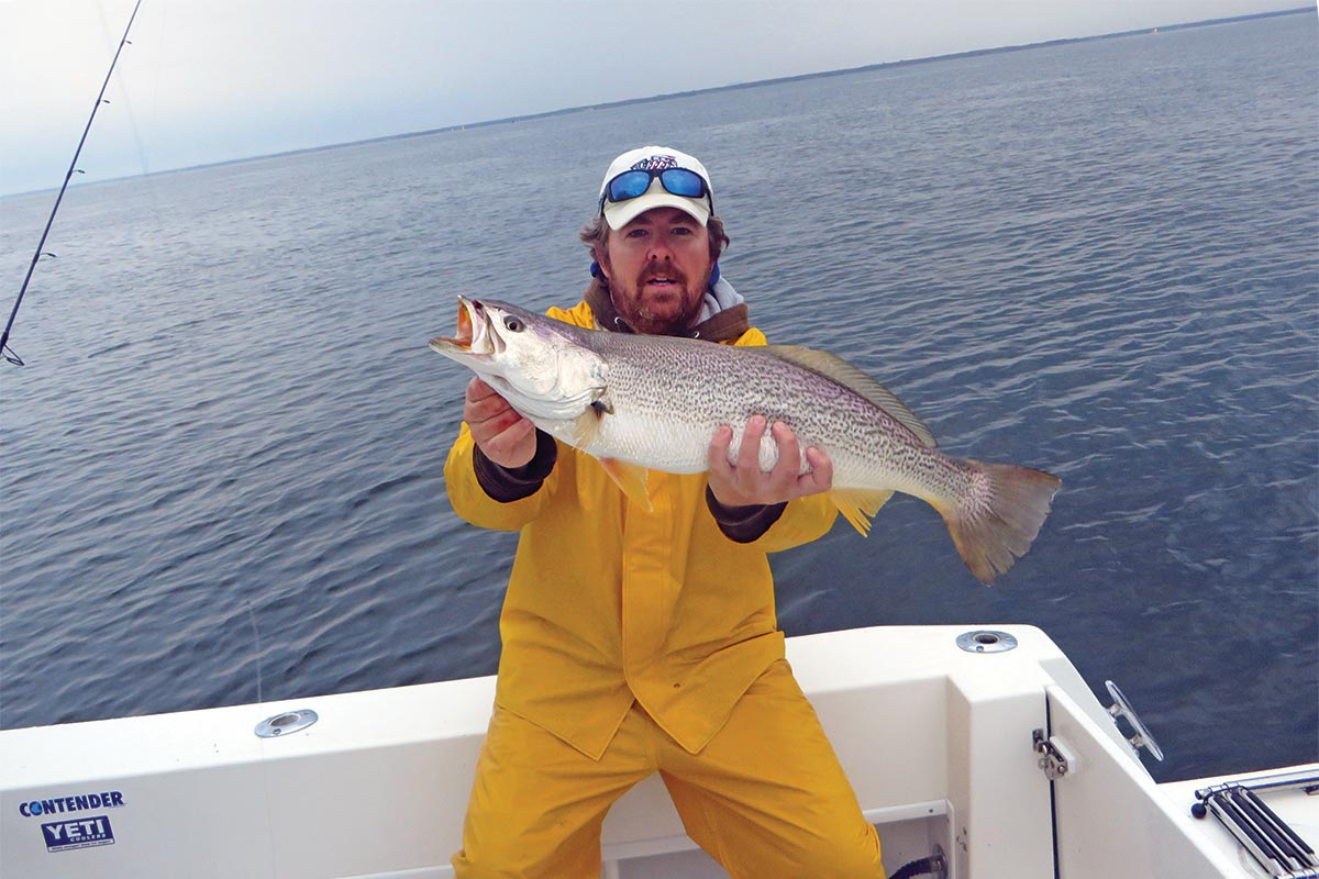 Man on a boat showing a weakfish