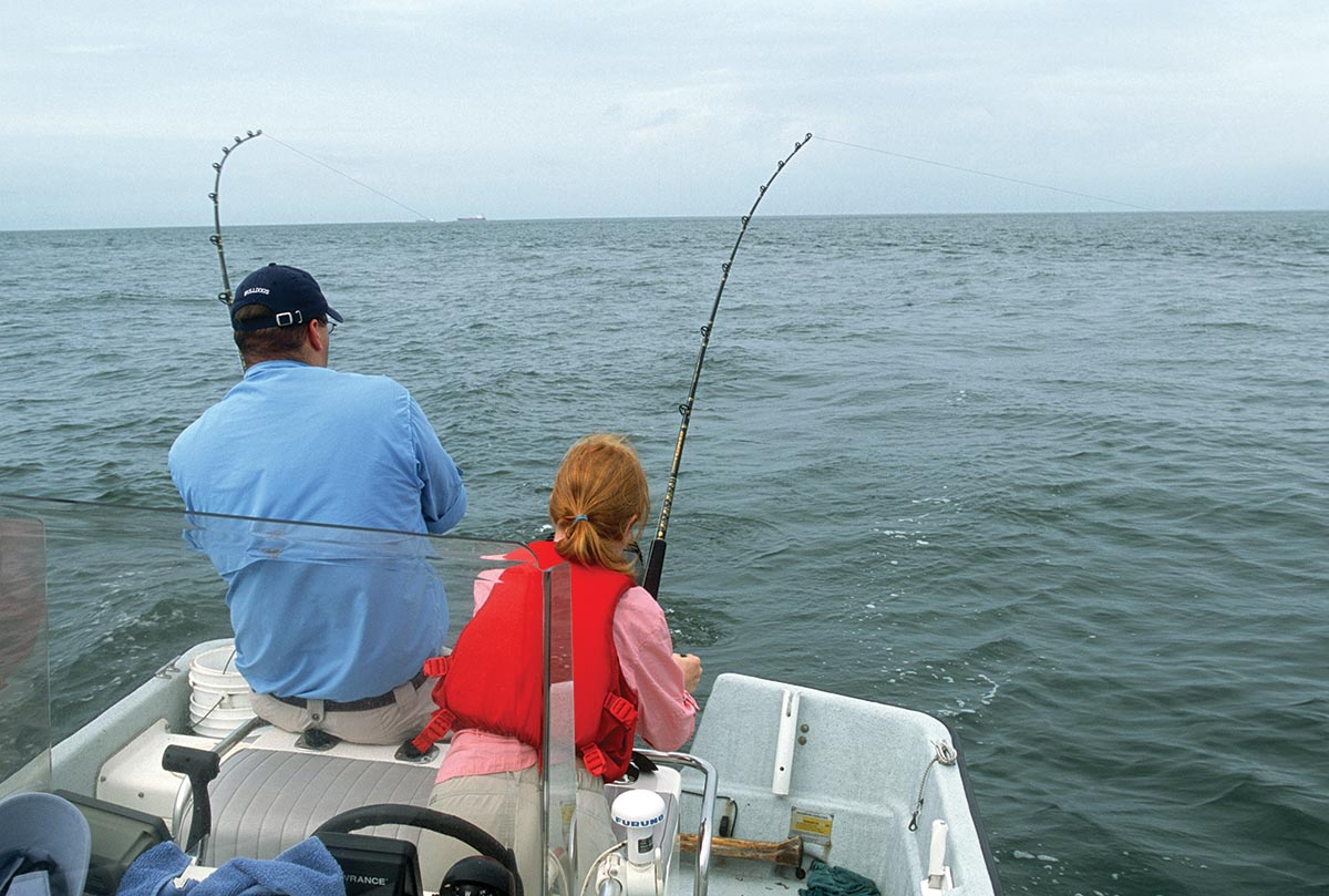 showing their back to the camera while facing the waters fishing