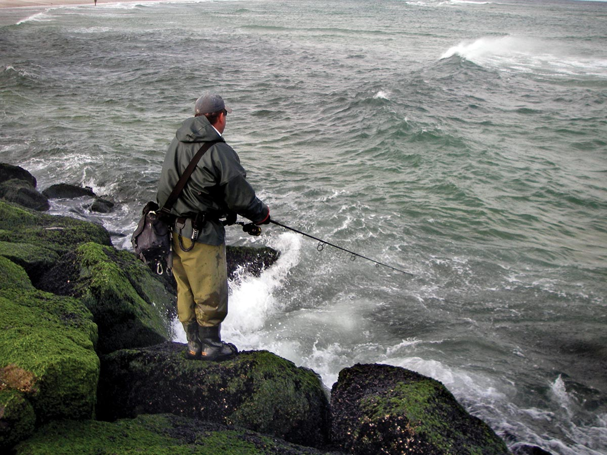 Man fishing using a rod standing on the rocks