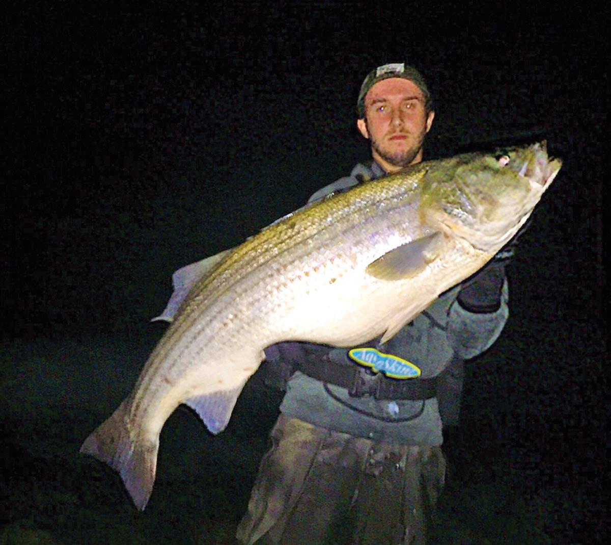 Matt Broderick holding a huge fish caught at night