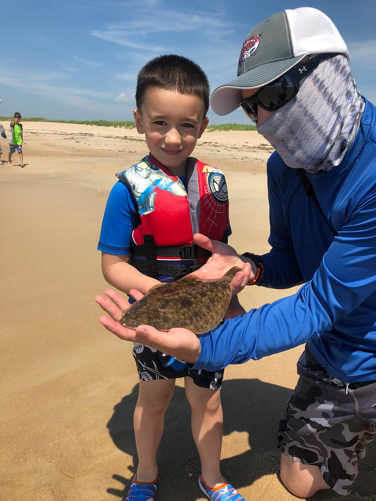 child showing off a fluke fish
