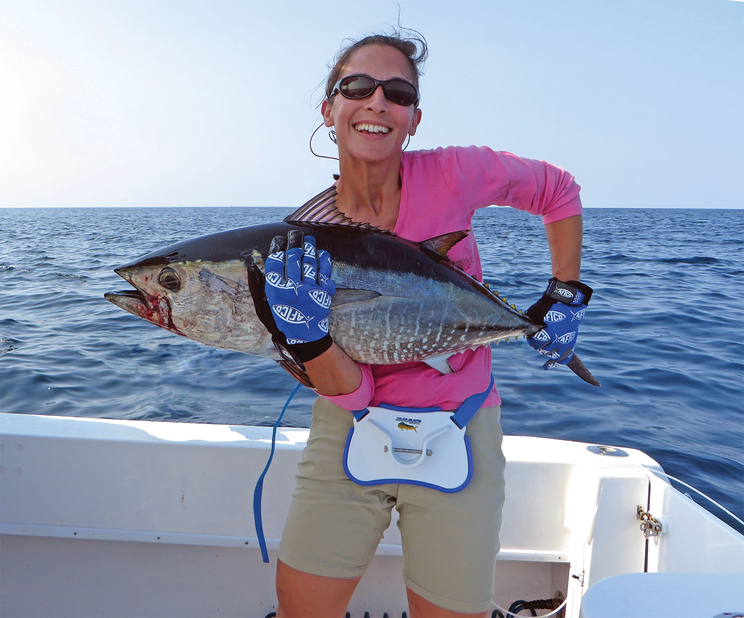 showing off a huge tuna with a huge smile and a pink shirt