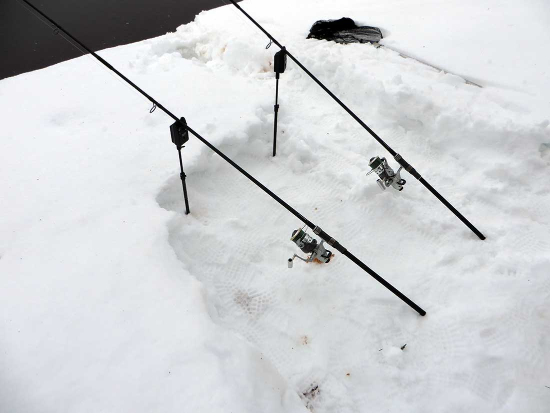 Two outfits are set up in the snow and loaded for carp fishing.