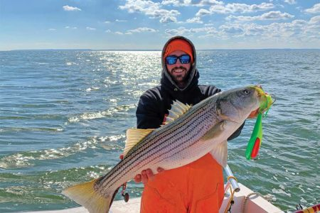 Doug Keeping shows off a nice striped bass caught on a spoon while trolling off the Jersey Shore.
